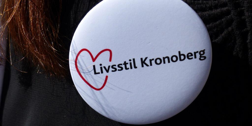 Fastnålad knapp med texten Livsstil Kronoberg på en tröja.